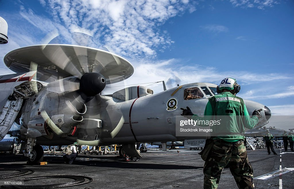 An aircraft director directs an E-2C Hawkeye aboard USS George Washington. : Stock Photo