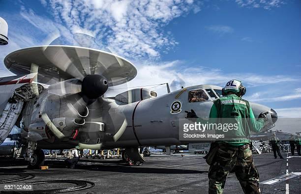 An aircraft director directs an E-2C Hawkeye aboard USS George Washington.