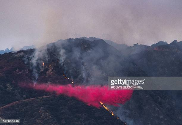 An aircraft drops fire redartant to prevent the advance of the San Gabriel Complex Fire in the Angeles National Forest near Duarte on June 21 2016...