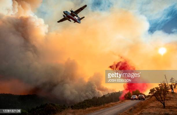 An aircraft drops fire retardant on a ridge during the Walbridge fire, part of the larger LNU Lightning Complex fire as flames continue to spread in...
