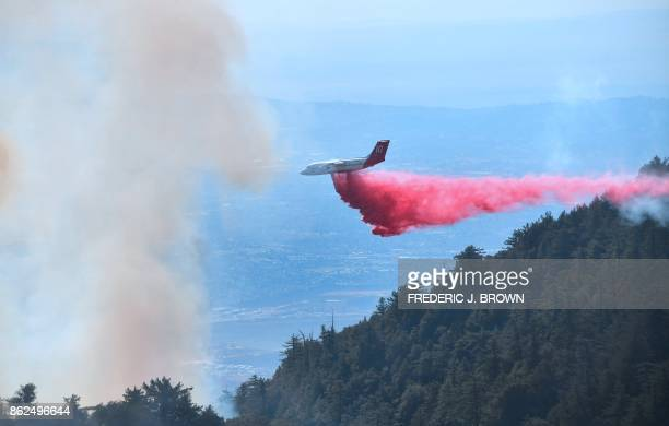 An aircraft drops fire retardant over a fire in the Angeles National Forest near Mt Wilson Observatory northeast of Los Angeles California on October...