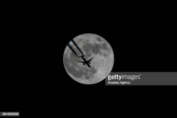 An aircraft flies in front of a full moon in Van Turkey on December 03 2017