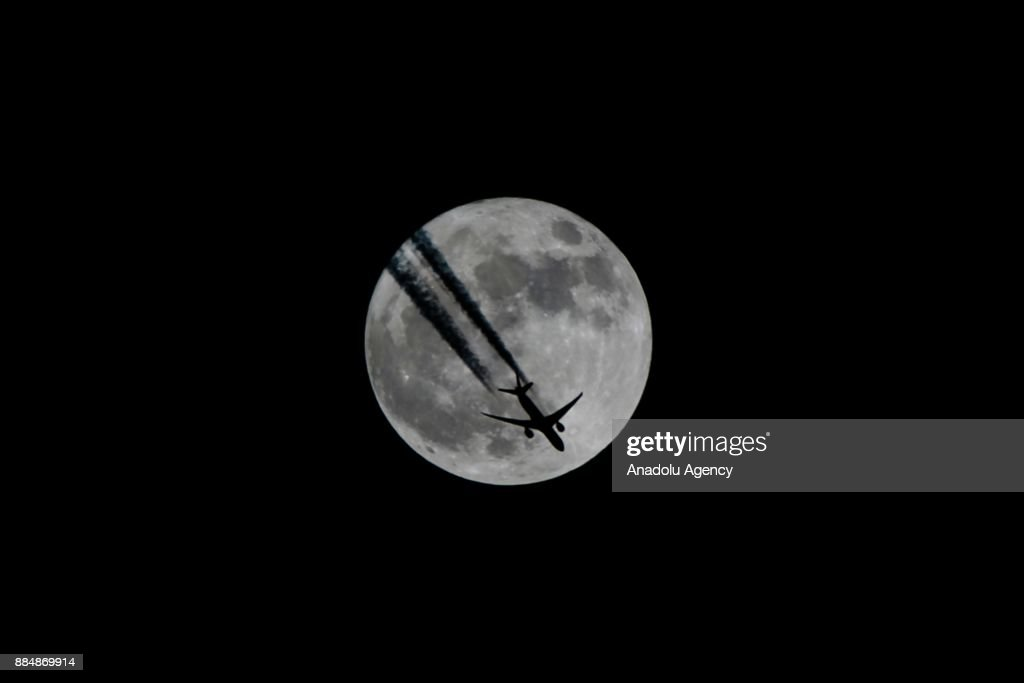 An aircraft flies in front of a full moon in Van, Turkey on December 03, 2017.