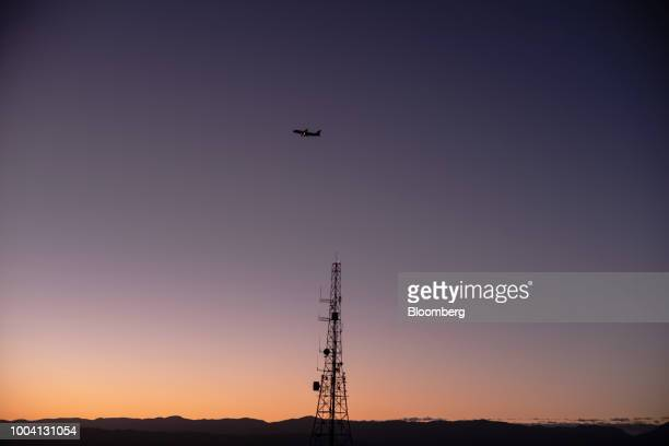 An aircraft flies over a telecommunications tower at dawn in Wellington New Zealand on Wednesday July 18 2018 New Zealand inflation picked up in the...