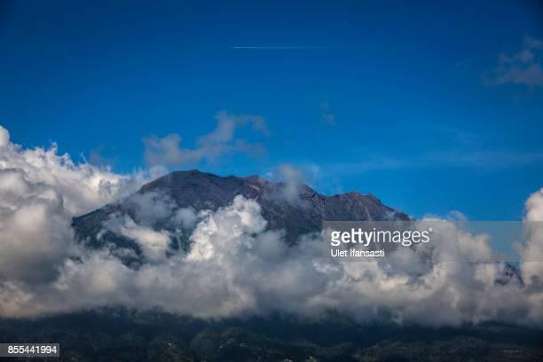KARANGASEM BALI INDONESIA SEPTEMBER 29 An aircraft flies over of mount Agung on September 29 2017 in Karangasem regency Island of Bali Indonesia...
