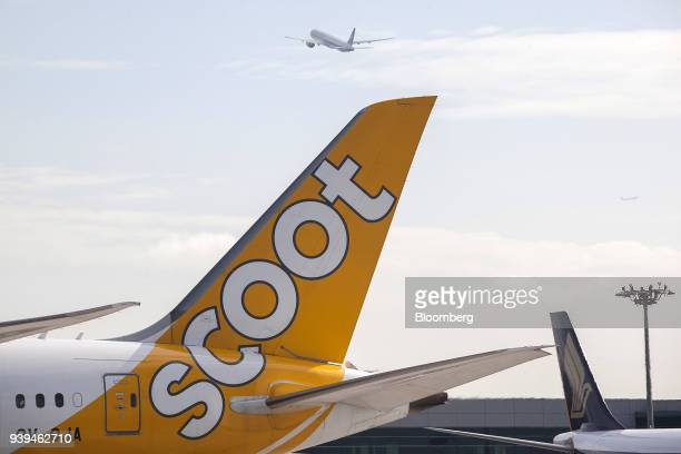 An aircraft is seen taking off as a Boeing Co 7879 Dreamliner aircraft operated by Scoot Pte a unit of Singapore Airlines Ltd sits on the tarmac at...