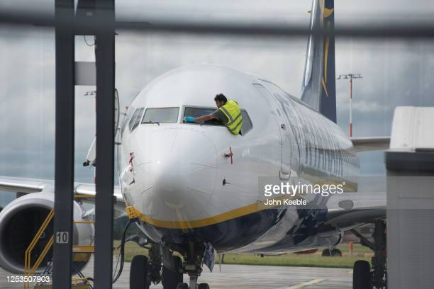 An aircraft maintenance person cleans the windscreen on a Ryanair aircraft at London Southend Airport on June 30, 2020 in Southend-on-Sea, England....