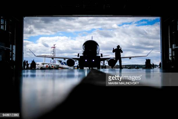 TOPSHOT An aircraft mechanic assists to park the Embraer175 airplane inside a hangar at the airport outside Minsk on April 19 2018