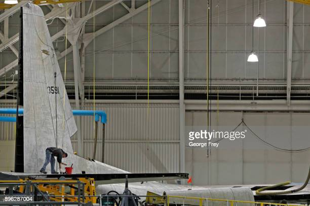 An aircraft mechanic works on the tail section of a C130 cargo plane on December 20 2017 at Hill Air Force base in Ogden Utah Hill Air Force Base has...