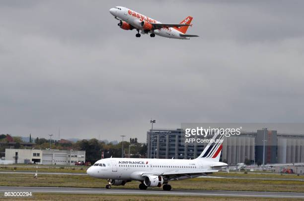 An aircraft of British lowcost airline EasyJet flies over an Air France aircraft parked on the tarmac of the ToulouseBlagnac airport near Toulouse on...