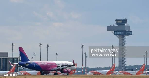 An aircraft of Hungarian low-cost airline Wizz Air touches down at Schoenefeld airport in Schoenefeld in front of the control tower of the...