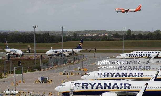 An aircraft operated by British no-frills airline Easyjet prepares to land beyond parked Ryanair aircraft at Stansted airport, northeast of London on...