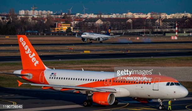 An aircraft operated by German flagcarrier Lufthansa lands past an aircraft operated by British low cost airline Easyjet at Tegel airport in Berlin...