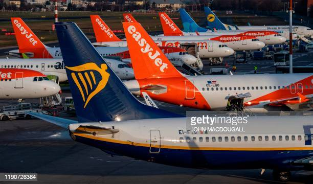 An aircraft operated by Irish lowcost airline Ryanair pulls out past aircraft operated by British low cost airline Easyjet at Tegel airport in Berlin...