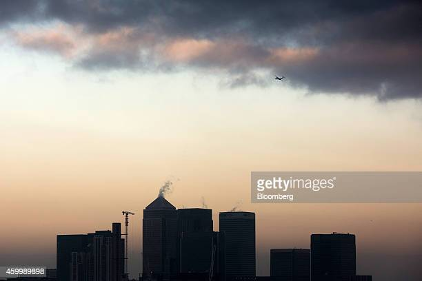 An aircraft passes above office towers including One Canada Square, center left, Citigroup Inc., center, and HSBC Holdings Plc, center right, at dawn...