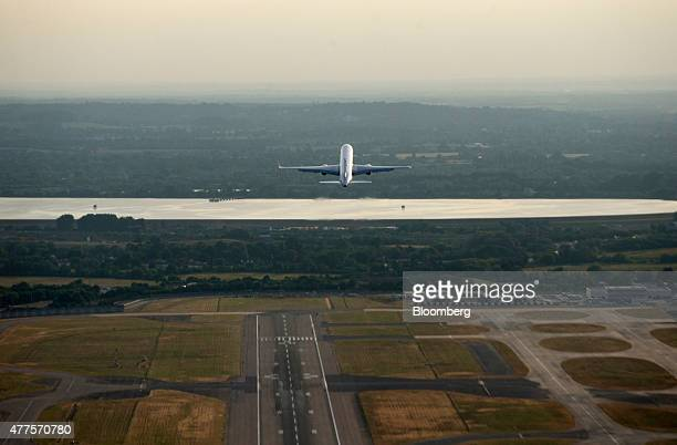 An aircraft rises into the sky after taking off from the north runway at London Heathrow Airport in this aerial photograph taken over London UK on...