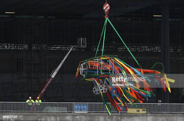 An aircraft shaped crown is lifted by a crane at the main terminal during the roofing ceremony at the new Airport Berlin Brandenburg International...