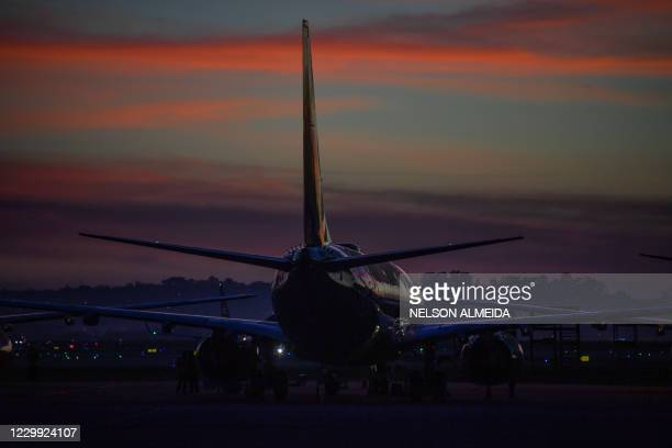 An aircraft sits on the tarmac before sunrise at Guarulhos International Airport, in Guarulhos, near Sao Paulo, Brazil, on December 03 amid the novel...