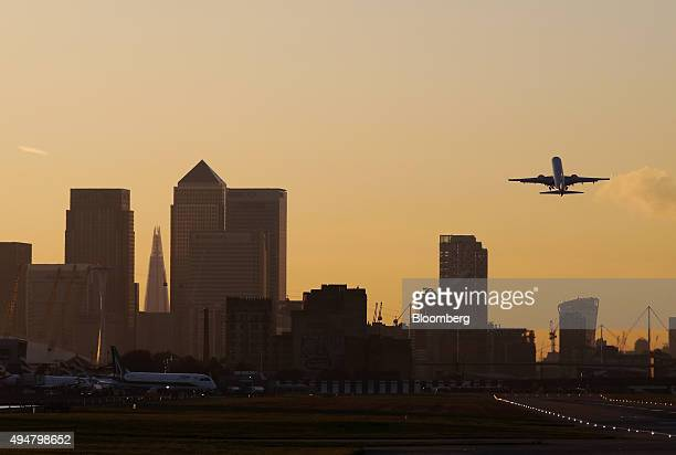 An aircraft takes off from London City Airport towards the direction of Canary Wharf business financial and shopping district in London UK on...