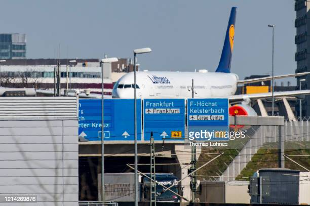An aircraft tug pulls a passenger airplane of German airline Lufthansa to parking position at a runway of the Frankfurt Airport on March 23, 2020 in...