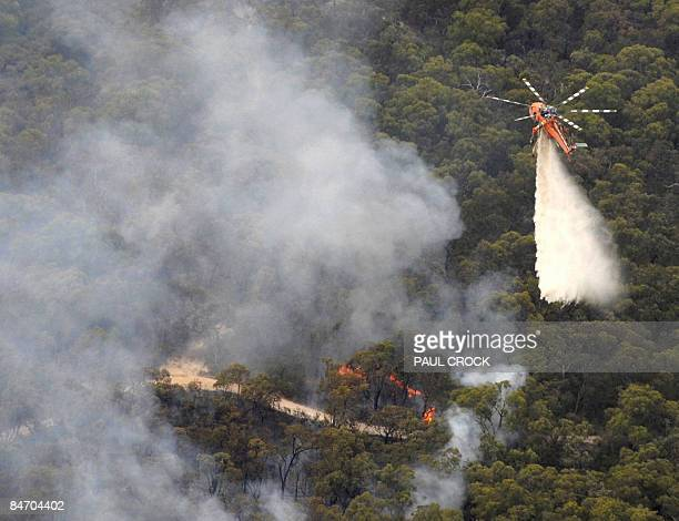 An aircrane firefighting aircraft dumps a load of water on the Bunyip Ridge wildfire which threatened electricity transmission lines near Bunyip West...