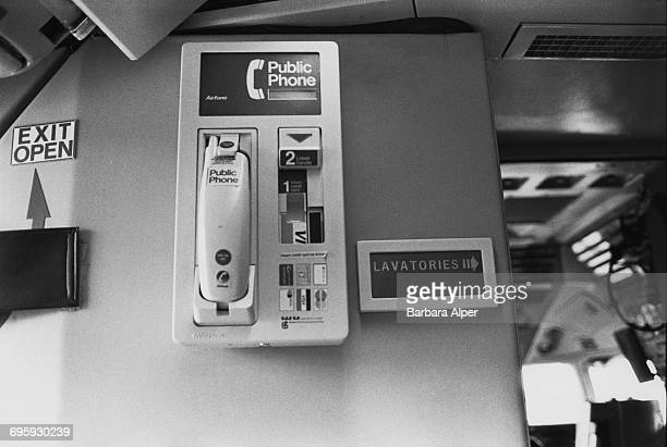 An Airfone public phone and a sign to the lavatories on board a passenger plane 1986