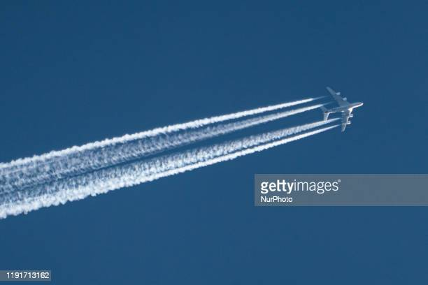 An airline commercial aircraft overflying in the blue sky long contrails of condensation behind it at very high altitude of 40000 feet The airliner...