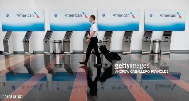 An airline employee walks past empty American Airlines checkin terminals at Ronald Reagan Washington National Airport in Arlington Virginia on May 12...