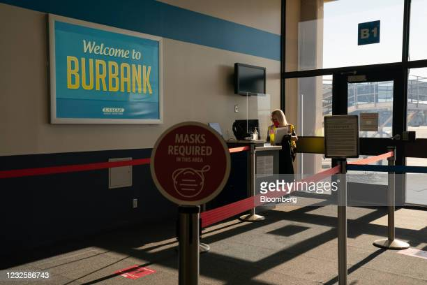 An airline employee wearing a protective mask works at a computer terminal inside Hollywood Burbank Airport in Burbank, California, U.S., on...