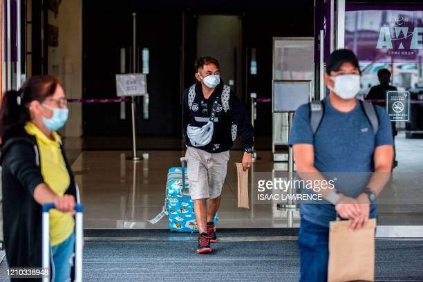 An airline passenger leaves a temporary COVID19 coronavirus testing centre set up at the AsiaWorldExpo for arriving passengers in Hong Kong on April...