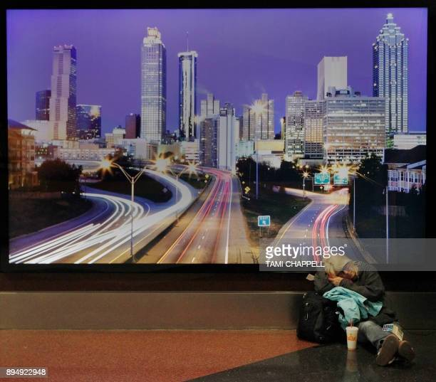 An airline passenger sleeps in front of a picture of Atlanta the day following a power outage caused by a fire at HartsfieldJackson Atlanta...