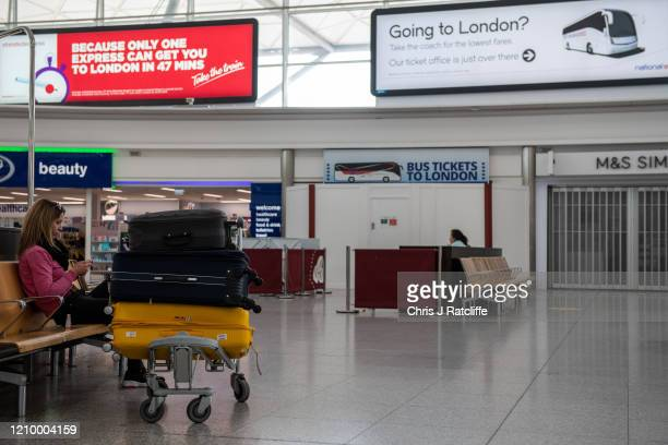 An airline passenger waits in a quiet airport lounge at Stansted Airport on April 15, 2020 in Stansted, Essex. Passenger travel has plummeted amid...