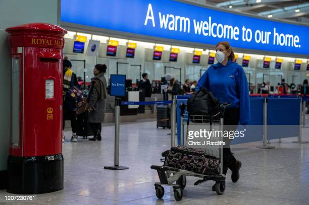An airline passenger wearing a face mask pushes her bags past a post box at Heathrow Terminal 5 departures as the outbreak of coronavirus intensifies...
