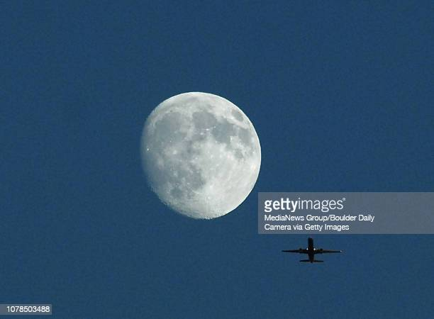 An Airliner flies by moon over Elizabeth Kennedy Stadium on Tuesday