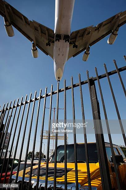 An airliner lands at Los Angeles International Airport as it files over parked cars on the eve of Thanksgiving on November 25 2009 in Los Angeles...