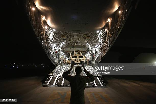 An airman guides a Humvee down a US Air Force C17 Globemaster cargo jet on January 9 2016 at a base in an undisclosed location in the Persian Gulf...