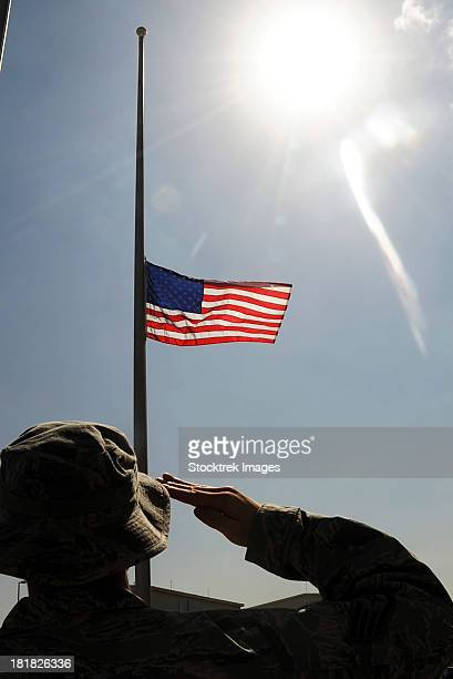 an airman salutes the american flag that is flying at half-mast. - half mast stock photos and pictures