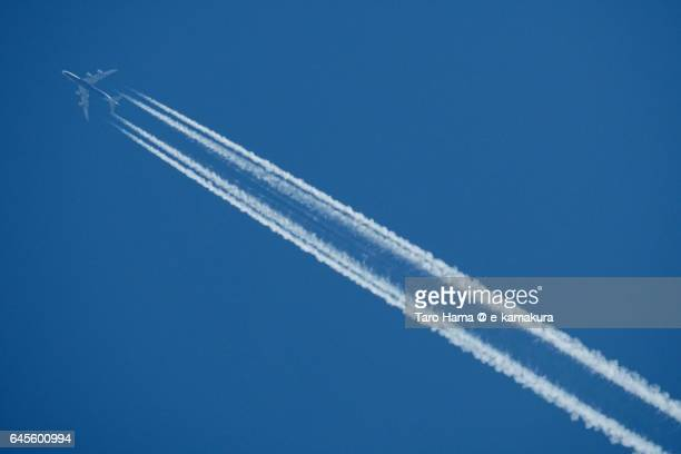 An airplane and vapor trail in the blue sky
