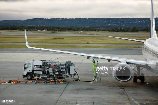 an airplane being refueled on the tarmac - refuelling stock pictures, royalty-free photos & images