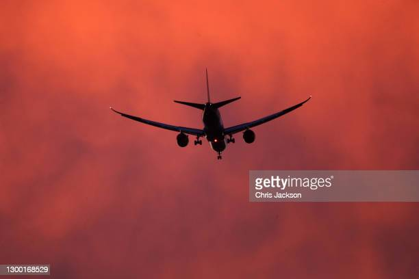 An airplane comes in to land at Heathrow Airport as the sun sets on February 03, 2021 in London, England .