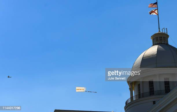 An airplane displaying a banner reading Abortion Is OK circles the Alabama State Capitol on May 15 2019 in Montgomery Alabama Today Alabama Gov Kay...