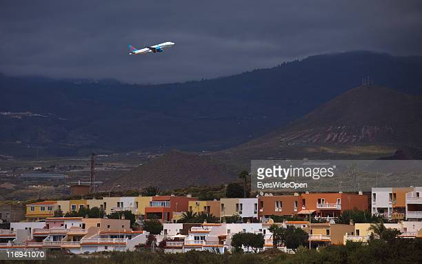 An airplane flies over houses after taking off from the Airport Reina Sofia on March 25 2011 in Tenerife Spain Tenerife is the biggest of the Canary...