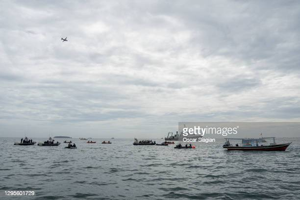 An airplane flies over Indonesian search and rescue teams scattered in several search points as they look for debris from the Sriwijaya Air flight...