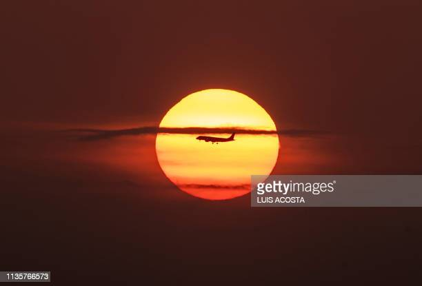 TOPSHOT An airplane flies over Panama Bay in Panama City during sunrise on April 8 2019