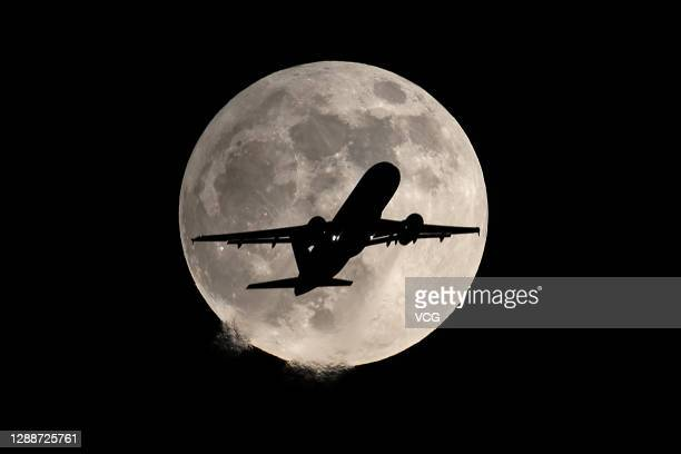 An airplane flies past the full moon during the penumbral lunar eclipse on November 30, 2020 in Shenyang, Liaoning Province of China.