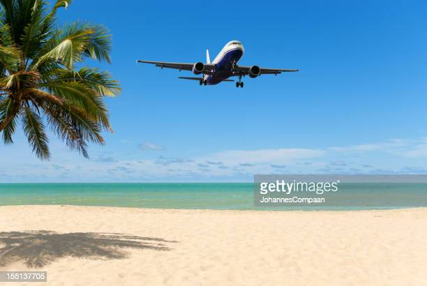An airplane flying close over a tropical beach