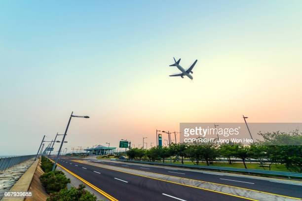 An airplane flying down over the expressway under the sunset sky