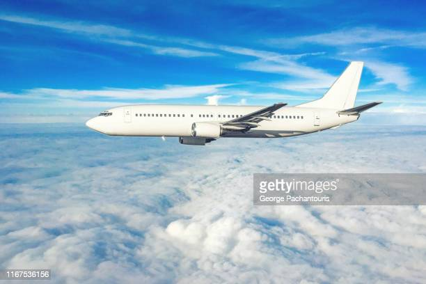 an airplane flying in the sky over clouds - fuselage stock pictures, royalty-free photos & images