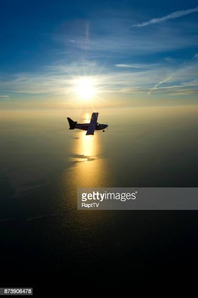 an airplane flying over the sea and sunset. - 自家用飛行機 ストックフォトと画像