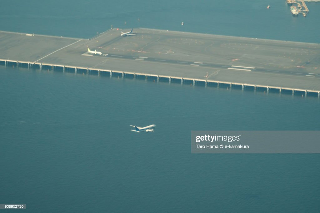 An airplane landing on 'C' runaway on Tokyo Haneda International Airport day time aerial view from airplane : ストックフォト
